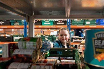 Foodbank volunteer stacking shelves